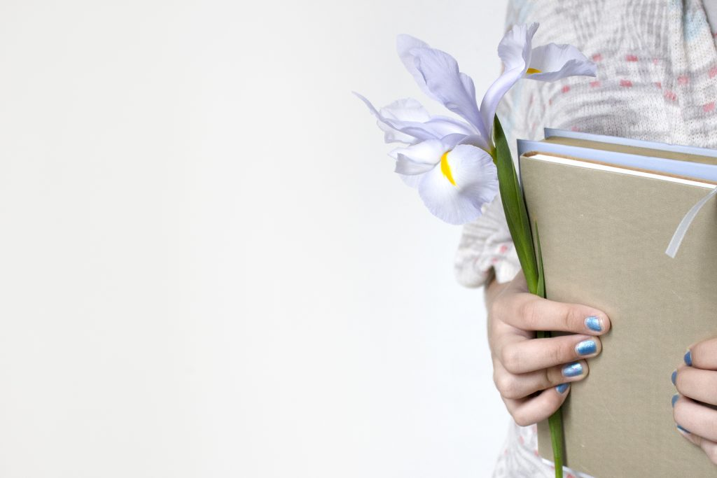 A woman holding a notebook and flower pen