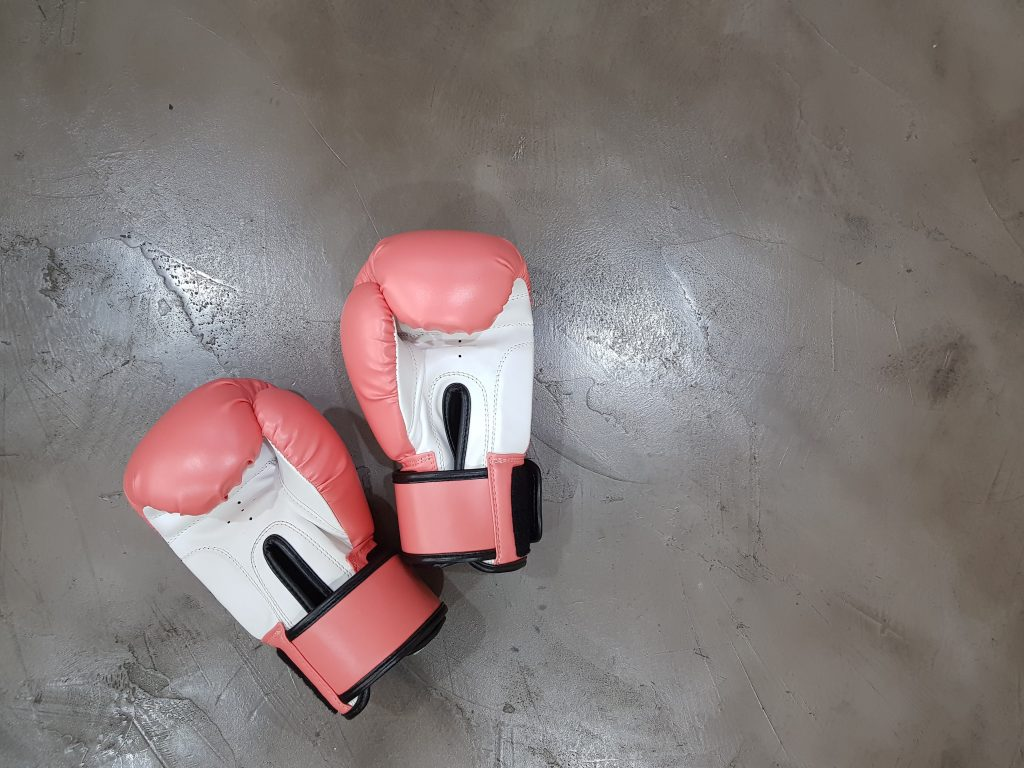 a pair of pink boxing gloves laying on cement representing a big fight
